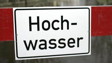 """Ein Schild mit der Aufschrift """"Hochwasser"""". (Motivbild)"""