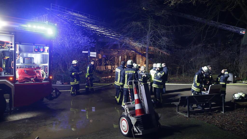 01.01.2020, Nordrhein-Westfalen, Krefeld: Feuerwehrleute stehen nach Löscharbeiten vor dem Affenhaus im Krefelder Zoo. Foto: David Young/dpa +++ dpa-Bildfunk +++