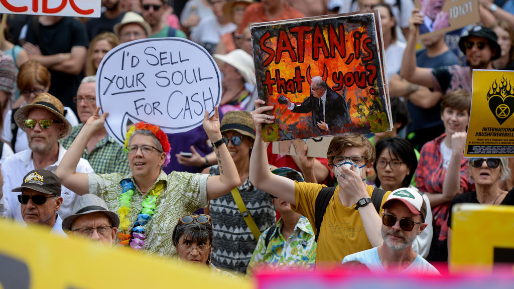 Protesters hold placards during a climate change rally in Sydney, Australia, January 10, 2020. AAP Image/Paul Braven/via REUTERS  ATTENTION EDITORS - THIS IMAGE WAS PROVIDED BY A THIRD PARTY. NO RESALES. NO ARCHIVE. AUSTRALIA OUT. NEW ZEALAND OUT.