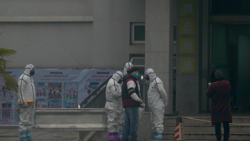 21.01.2020, China, Wuhan: Mitarbeiter in Schutzanzügen stehen vor dem Wuhan Medical Treatment Center, in dem ein Patient mit Verdacht auf den neuartigen Corona-Virus behandelt wurde. Foto: Dake Kang/AP/dpa +++ dpa-Bildfunk +++