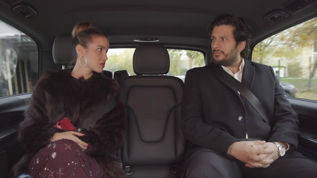 AWZ: Chiara und Maximilian sitzen nebeneinander im Auto und schauen sich an.
