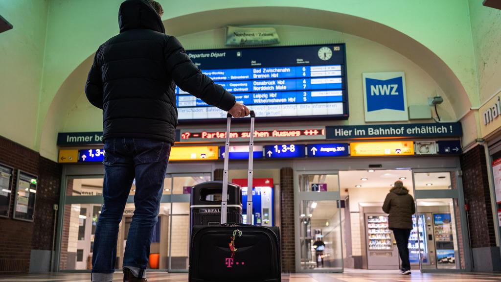 10.02.2020, Niedersachsen, Oldenburg: Ein Reisender steht am frühen Morgen im Oldenburger Hauptbahnhof und schauet zur Anzeigetafel der Deutschen Bahn hoch, auf der wegen den Folgen des Sturmtiefs ·Sabine· Verspätungen und Ausfälle der Züge angezeigt