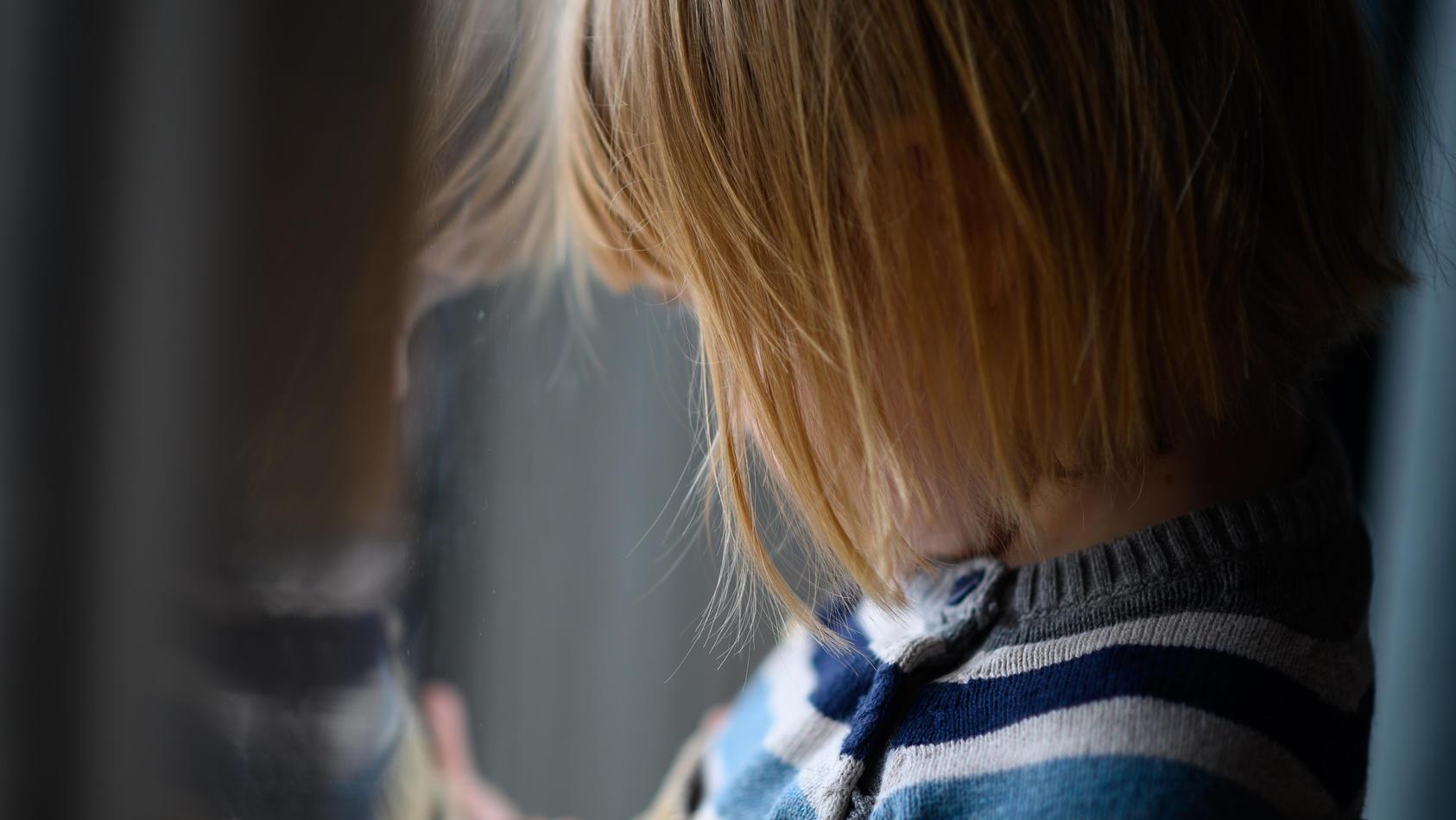Kind schaut aus dem Fenster
