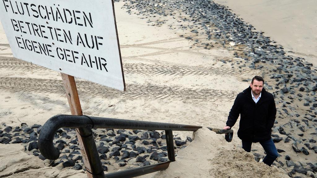 """13.02.2020, Niedersachsen, Wangerooge: Ein Schild mit der Aufschrift """"Flutschäden, Betreten auf eigene Gefahr"""" ist am Strand zu sehen. Bürgermeister Marcel Fangohr (parteilos) steht im Hintergrund an der Abbruchkante des Strandes. Die Sturmflut der l"""