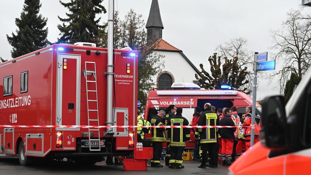 24.02.2020, Hessen, Volkmarsen: Feuerwehrleute und Notfallsanitäter stehen  hinter einem Absperrband an der Stelle, an der ein Auto in einen Rosenmontagsumzug gefahren ist. Dabei gab es mehrere Verletzte. Die Polizei hat nach eigenen Angaben noch kei