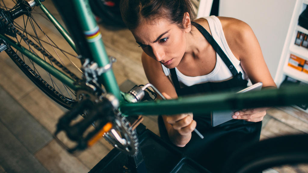 Frau macht Fahrrad fit für den Frühling