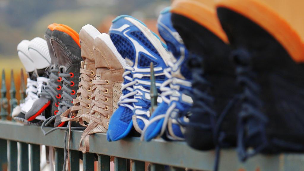 Gewaschene Sneakers trocknen auf dem Gartenzaun