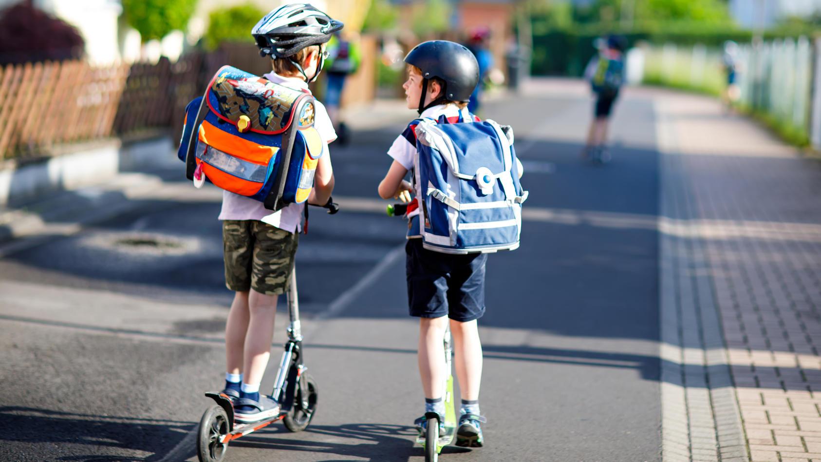 Auf dem Weg zur Schule mit dem Kinderroller.