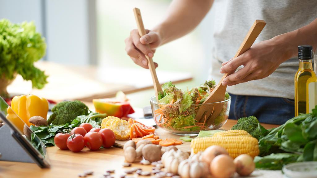 Ein Mann mixt in einer Salatschüssel seinen Salat, um ihn herum liegen verschiedene Gemüsesorten.