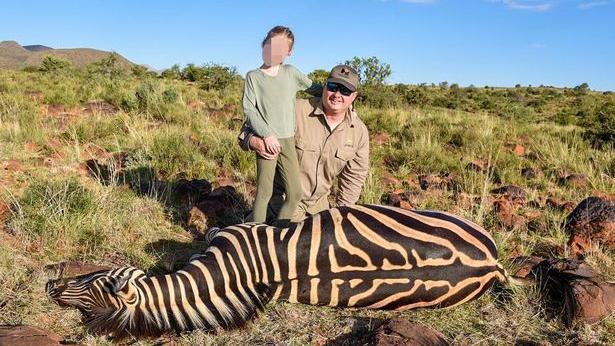 Ein neunjähriges Mädchen posiert neben einem toten Zebra.