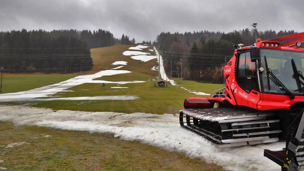 """ARCHIV - 03.02.2020, Bayern, Thalkirchdorf: Eine Pistenraupe steht auf einer Skipiste, die bei Tauwetter noch teilweise mit Schneeresten bedeckt ist. (Zu dpa """"Winter in Europa war der wärmste seit Beginn der Aufzeichnungen"""") Foto: Benjamin Liss/dpa +"""
