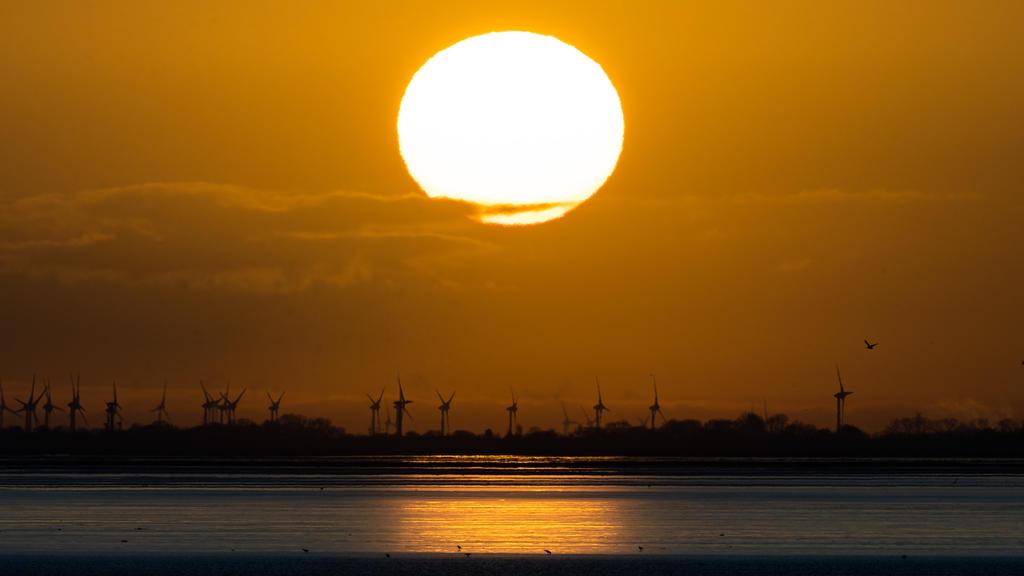 27.02.2020, Niedersachsen, Norderney: Der Sonnenaufgang ist über demFestland an der ostfriesischen Nordseeküste zu sehen. Fotografiert von der Insel Norderney aus. Foto: Mohssen Assanimoghaddam/dpa +++ dpa-Bildfunk +++