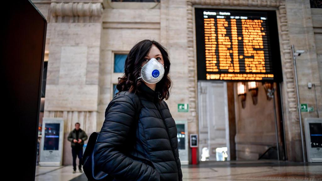 08.03.2020, Italien, Mailand: Eine Passantin mit Atemschutz steht im Hauptbahnhof. Im Kampf gegen das neue Coronavirus schränkt Italien die Bewegungsfreiheit von Bürgern im Norden drastisch ein. Die Menschen in der wirtschaftsstarken Lombardei und 14