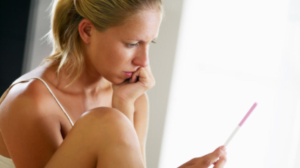 woman looking at pregnancy test. Side view, Copy space