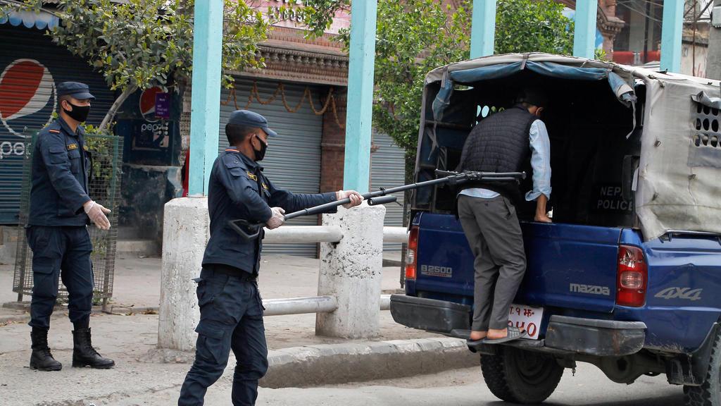 HANDOUT - 27.03.2020, Nepal, Kathmandu: Ein Polizist benutzt einen Abstandshalter, um einen Mann in ein Polizeifahrzeug zu schieben. Foto: Manoj Bhusan Khadka/Polizei Nepal/dpa - ACHTUNG: Nur zur redaktionellen Verwendung im Zusammenhang mit der aktu