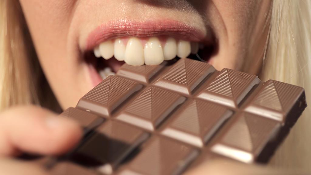 Frau beißt in Schokoladentafel