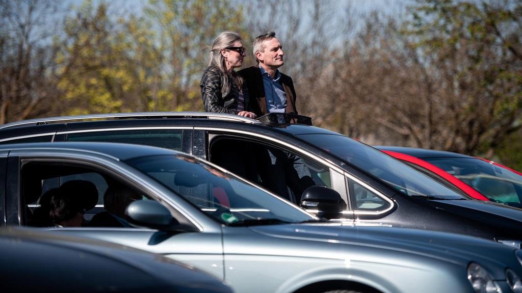 10.04.2020, Nordrhein-Westfalen, Düsseldorf: Oberbürgermeister Thomas Geisel sitzt mit seiner Frau Vera in seinem Auto und guckt aus dem Dachfenster Richtung Bühne. Trotz der Corona-Krise sollen Gläubige in einem Düsseldorfer Autokino Ostergottesdien