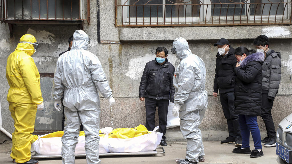FILE - In this Feb. 1, 2020, file photo, funeral home workers remove the body of a person suspected to have died from the coronavirus outbreak from a residential building in Wuhan in central China's Hubei Province. The central Chinese city of Wuhan h