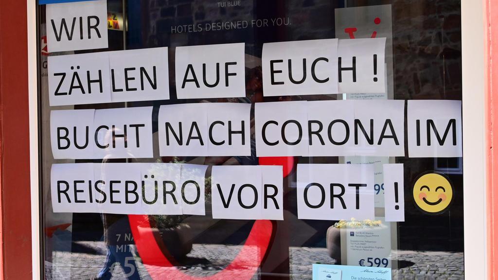 """10.04.2020, Hessen, Fritzlar: Ein Reisebüro in der Altstadt zählt laut Schaufensteraushang darauf, dass die Kunden nach der Coronakrise bei ihnen """"vor Ort"""" Reisen buchen werden. Foto: Uwe Zucchi/dpa +++ dpa-Bildfunk +++"""