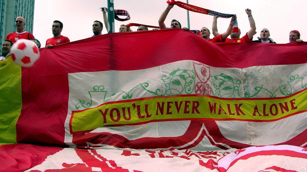Liverpooler Fans mit einer riesigen Vereinsfahne, auf der die Vereinshymne zu lesen ist: You ll never walk alone