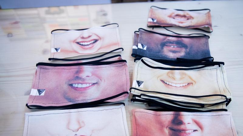 Fotomasken als Mund-Nase-Schutz liegen in einer Textildruckerei auf einem Tisch. Foto: Christian Charisius/dpa