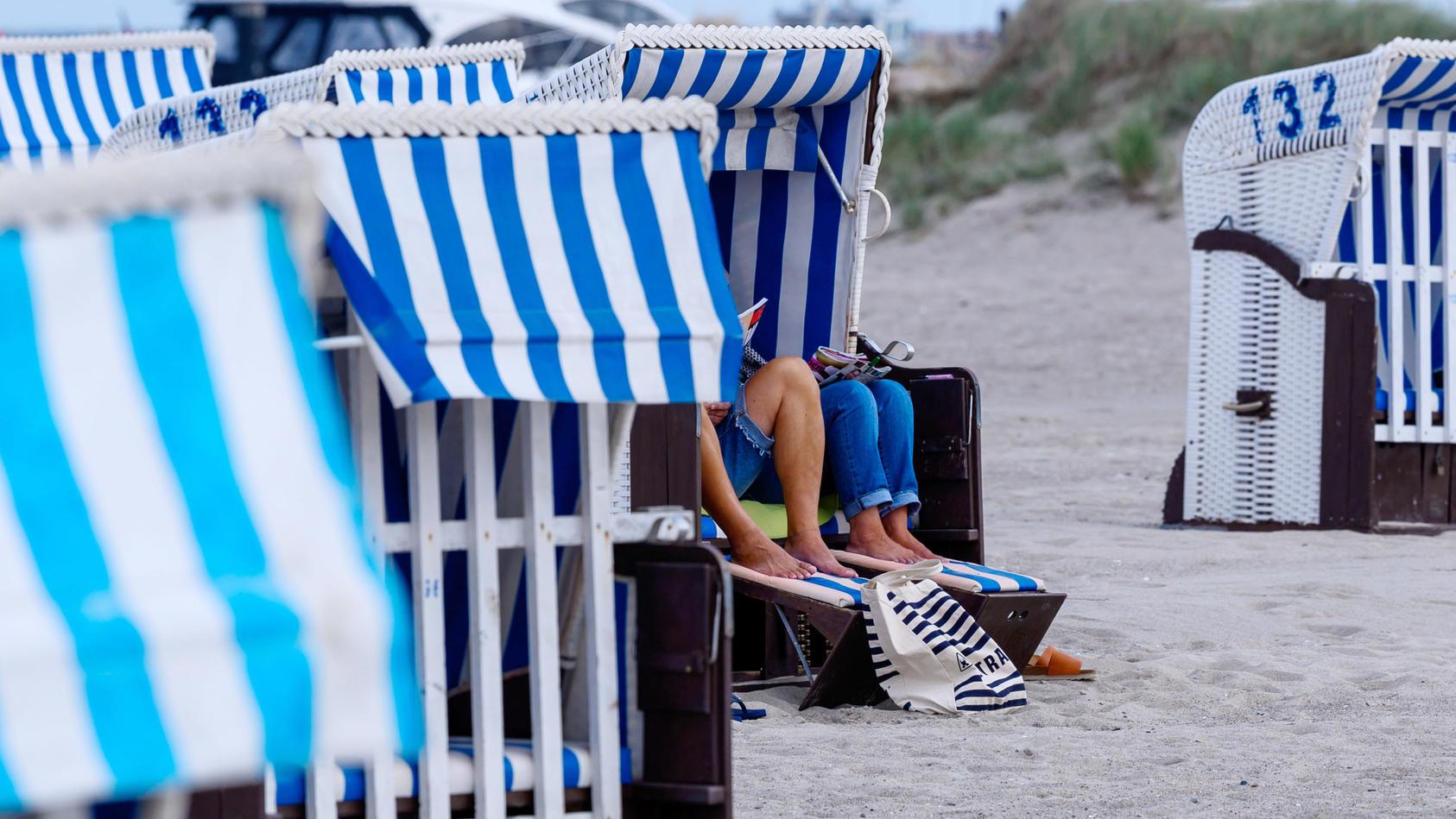 Am Strand sitzen Urlauber in einem Strandkorb