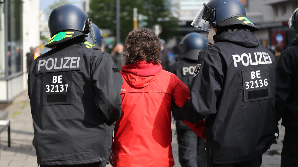 02.05.2020, Berlin: Ein Demonstrant wird in der nähe des Rosa-Luxemburg-Platz bei einer Kundgebung gegen die Corona-Einschränkungen von Polizisten abgeführt. Verschiedene Kundgebungen finden auf dem Rosa-Luxemburg-Platz statt. Zu einer der Kundgebung