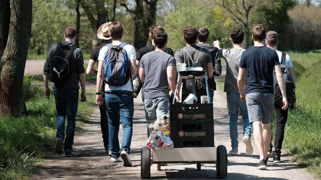 Eine Gruppe junger Männer feiert den Vatertag mit einem mit Bier gefüllten Bollerwagen.