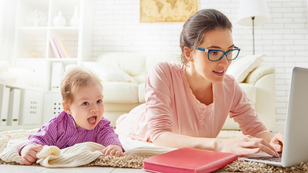 Eine Frau mit Baby arbeitet in der Elternzeit
