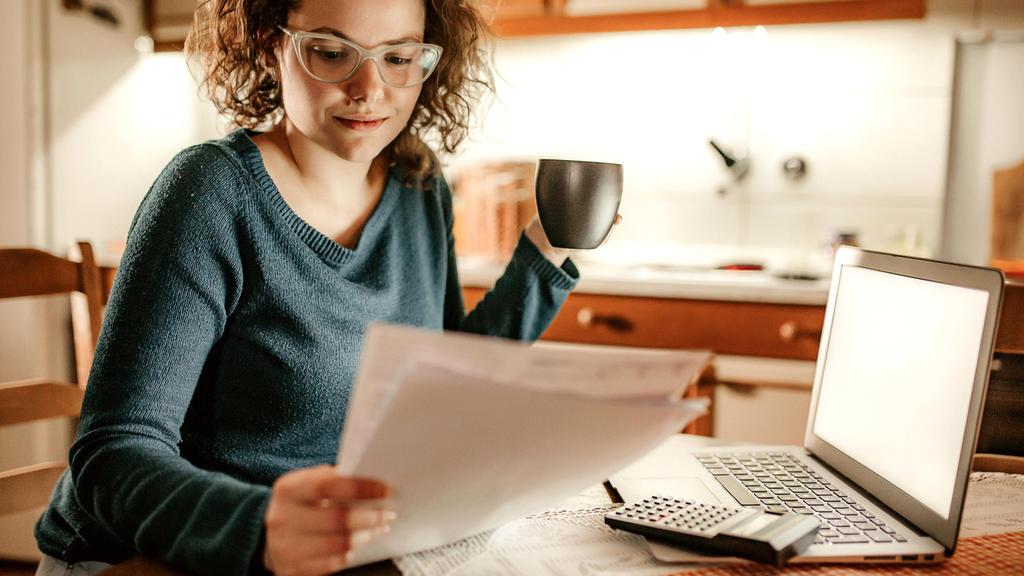 Frau rechnet ihre Finanzen durch mit einem Taschenrechner