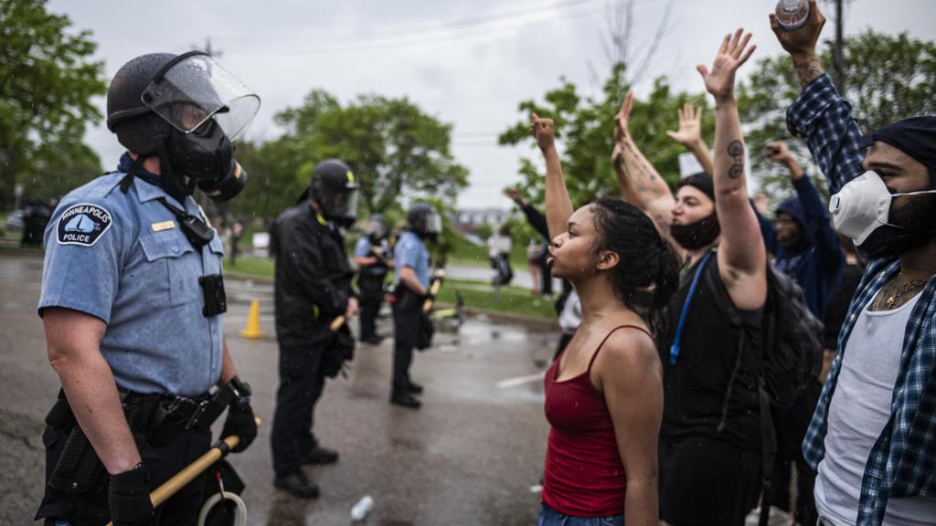 dpatopbilder - 26.05.2020, USA, Minneapolis: Demonstranten und Polizisten stehen sich während eines Protests für einen Mann afroamerikanischer Abstammung demonstrierten, der nach der Festnahme durch die Polizei verstarb, gegenüber. Der weiße Polizist