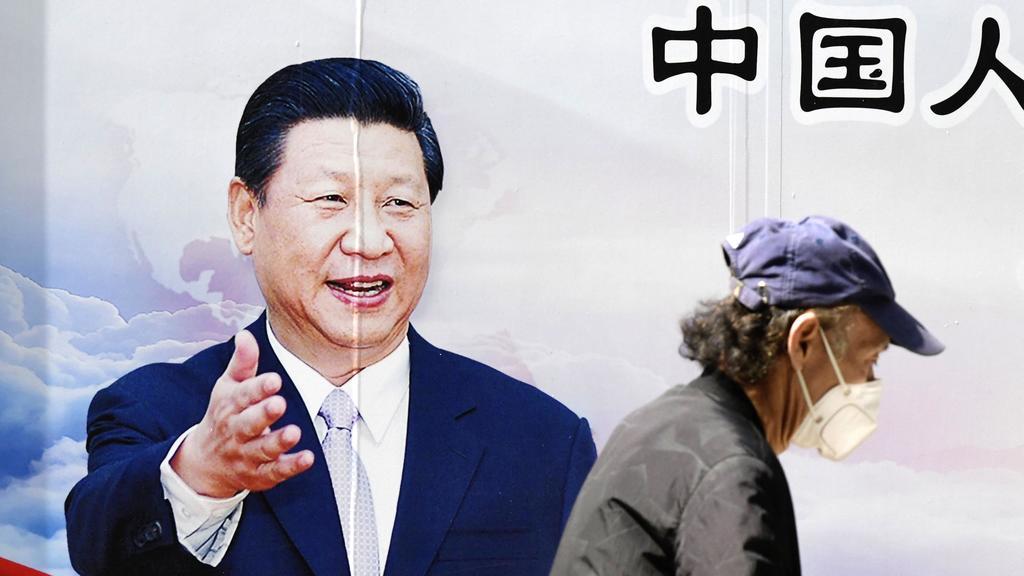 Ein Mann spaziert mit einer Maske an einem Plakat von Chinas Präsident Xinping vorbei. Foto: -/kyodo/dpa +++ dpa-Bildfunk +++