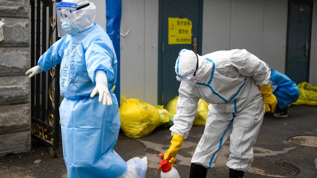 China, Jilin: Ein medizinischer Mitarbeiter desinfiziert einen anderen, der kommt, um die COVID-19-Proben für einen Nukleinsäuretest im Zentrum für Krankheitskontrolle und Prävention einzureichen. Foto: Yan Linyun/XinHua/dpa