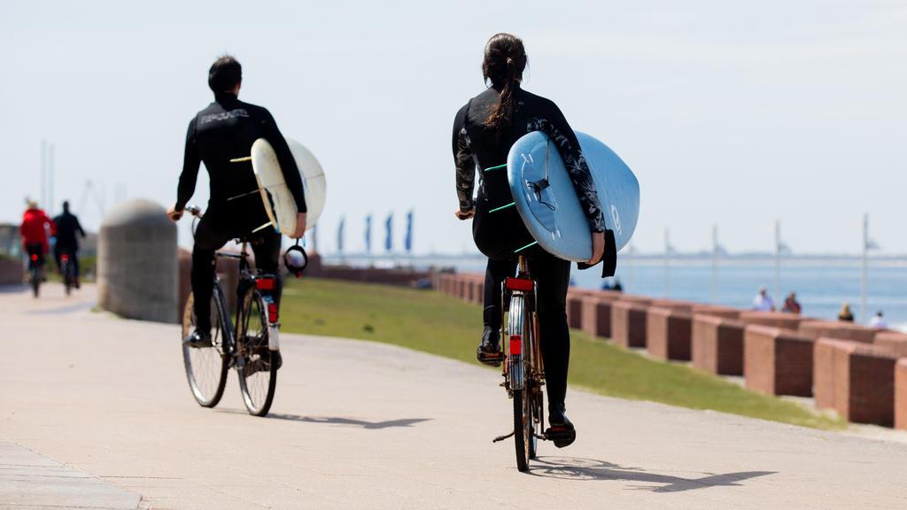 26.05.2020, Niedersachsen, Norderney: Zwei Surfer auf Fahrrädern fahren mit ihren Surfbrettern auf der Promenade am Meer entlang. Foto: Rolf Vennenbernd/dpa +++ dpa-Bildfunk +++