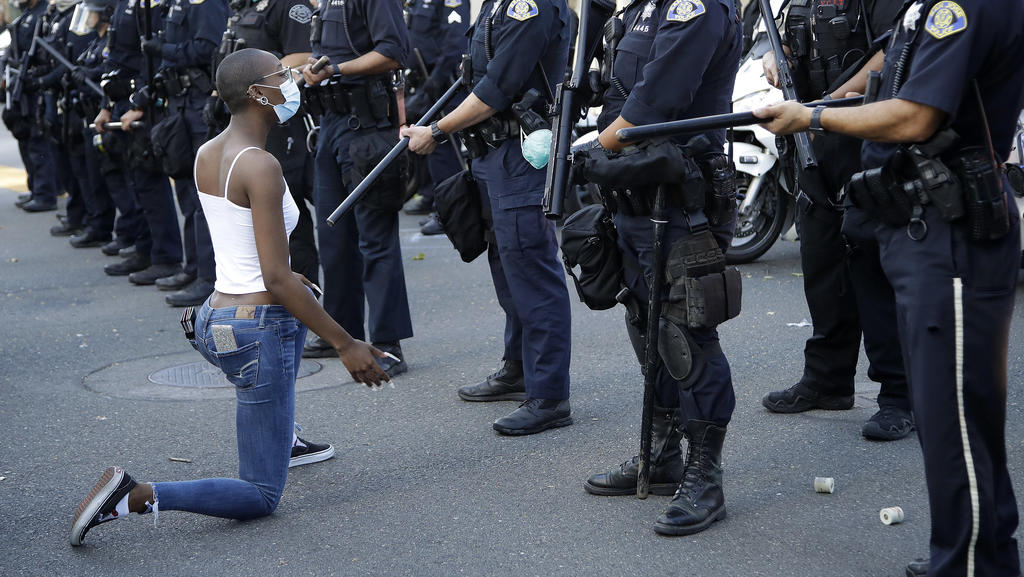 A masked protester kneels before San Jose police on Friday, May 29, 2020, in San Jose, Calif., in response to the death of George Floyd in police custody on Memorial Day in Minneapolis. (AP Photo/Ben Margot)