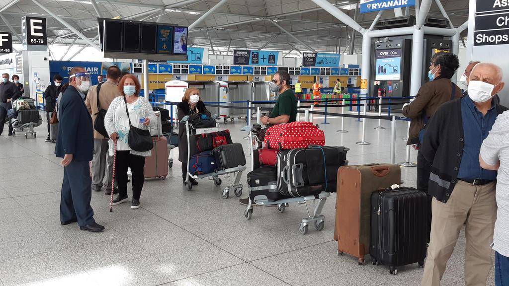 03.06.2020, Großbritannien, Stansted: Passagiere stehen am Flughafen Stansted Essex Schlange für einen Flug nach Adana in der Türkei. Geplant war bisher, vom 8. Juni an eine zweiwöchige Quarantäne für alle Reisenden einzuführen, die nach Großbriannie