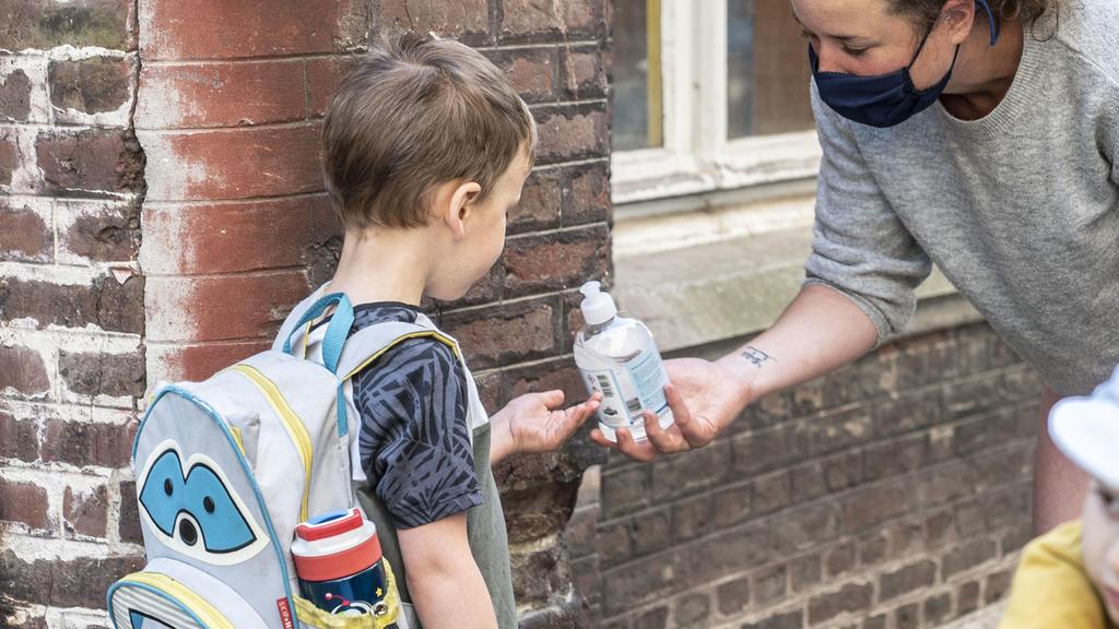 """ILLUSTRATION - 02.06.2020, Belgien, Gent: Eine Lehrerin gibt einem Schüler Desinfektionsmittel am Eingang der """"De Kleine Icarus""""-Schule. Belgien befindet sich in der zweiten Phase der Lockerungen während der Corona-Pandemie. Im Zuge der Lockerungen g"""