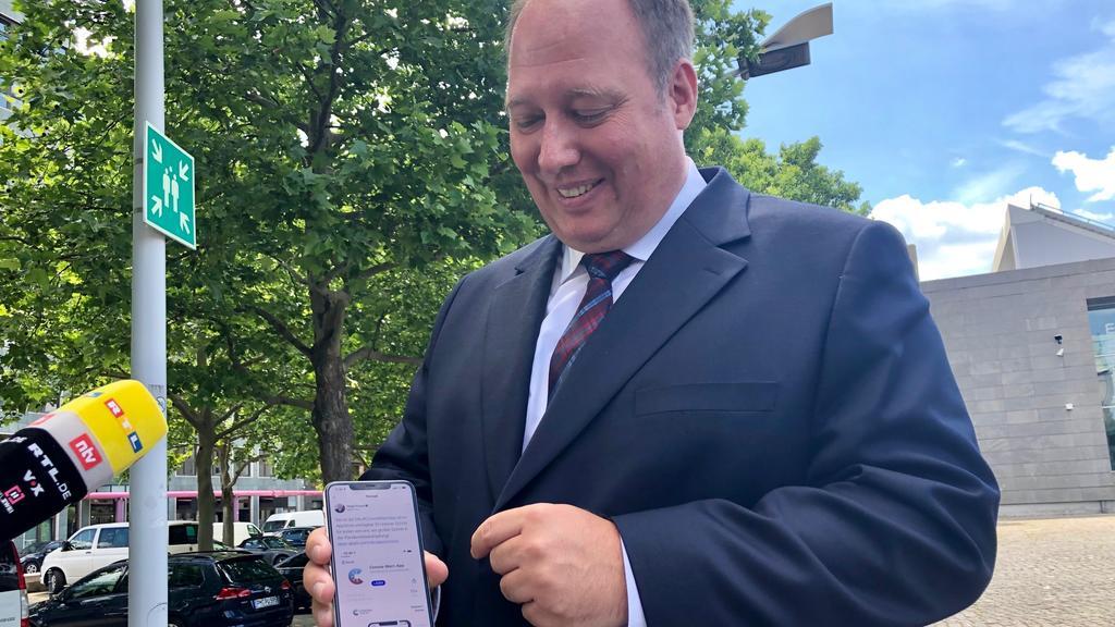 Helge Braun zeigt die Corona-Warn-App auf seinem Smartphone