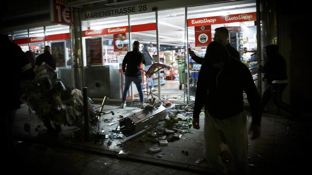 21.06.2020, Baden-Württemberg, Stuttgart: Menschen stehen vor einem geplünderten Geschäft in der Marienstraße. Bei Auseinandersetzungen mit der Polizei haben dutzende gewalttätige Kleingruppen die Innenstadt verwüstet und mehrere Beamte verletzt. Fot