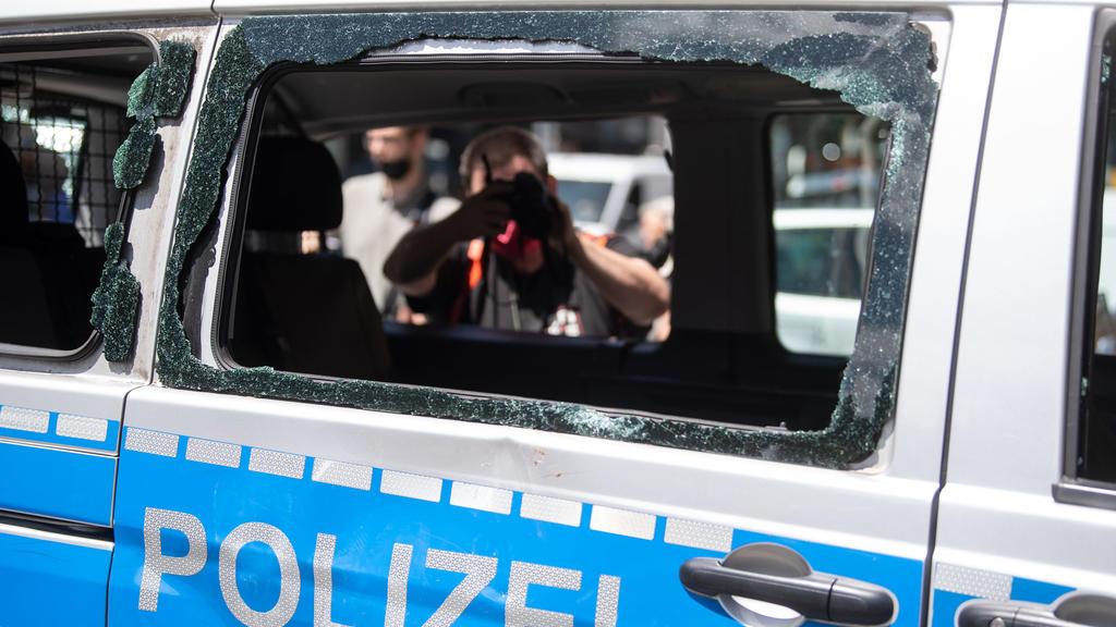 22.06.2020, Baden-Württemberg, Stuttgart: Ein während der nächtlichen Randale in Stuttgart beschädigtes Polizeiauto, das zuvor für einen Ortsbesuch von Bundesinnenminister Seehofer an den Ort der Randale gebracht worden war, wird von einem Fotografen