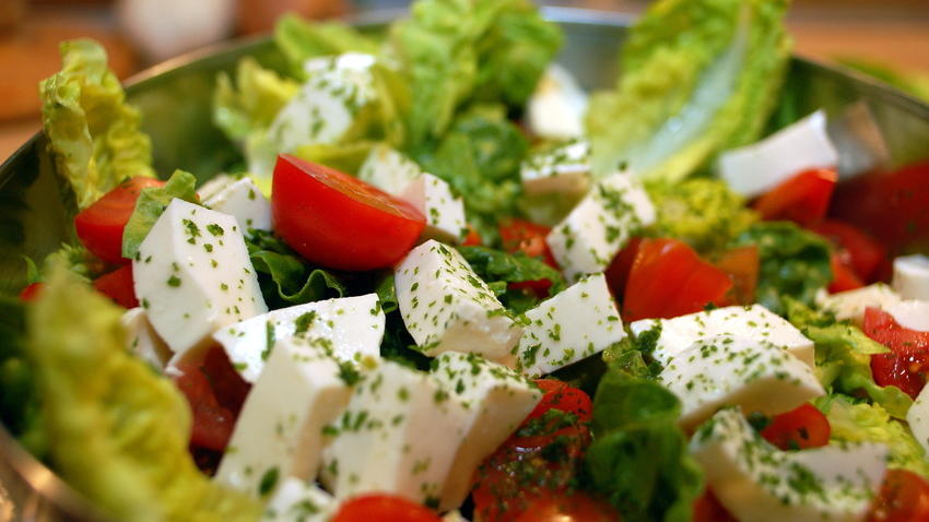Salat mit Tomaten und Mozzarella angerichtet in einer Salatschüssel.