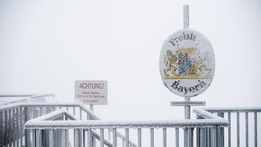 """dpatopbilder - 26.08.2018, Bayern, Grainau: Schnee und Eis bedecken auf dem Gipfel der Zugspitze ein Schild mit der Aufschrift """"Freistaat Bayern"""". Foto: Sven Hoppe/dpa +++ dpa-Bildfunk +++"""