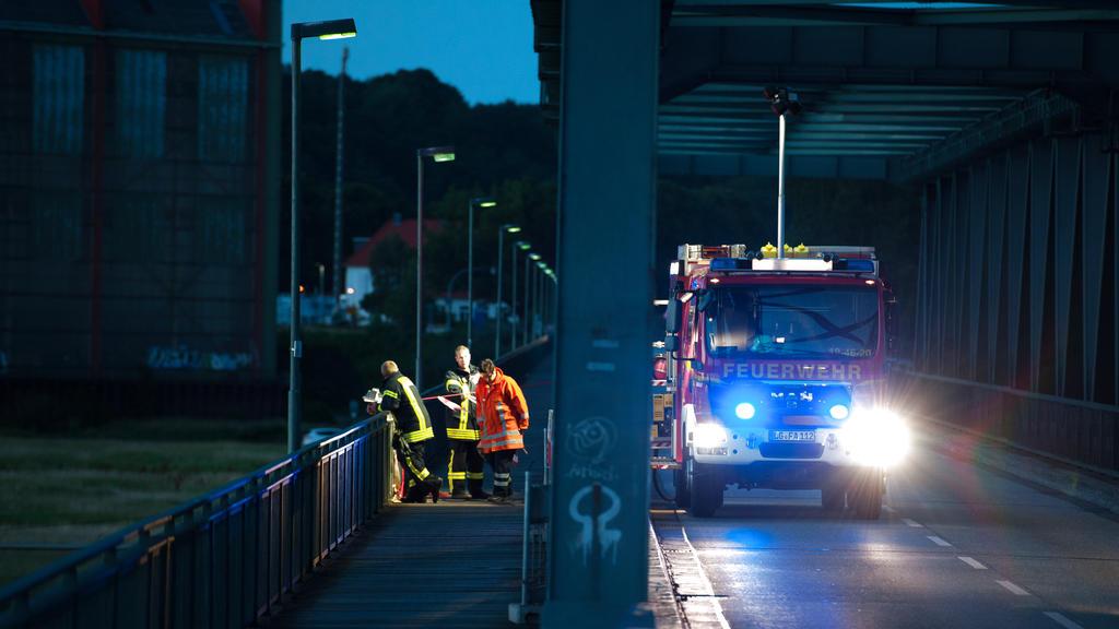 Ein Fahrzeug der Feuerwehr steht am 31.07.2015 bei Hohnstorf/Elbe (Niedersachsen) auf einer Brücke, die über die Elbe nach Lauenburg (Schleswig-Holstein) führt. Im Fall der verschwundenen Familie aus Drage (Niedersachsen) prüft die Polizei einen Zusa