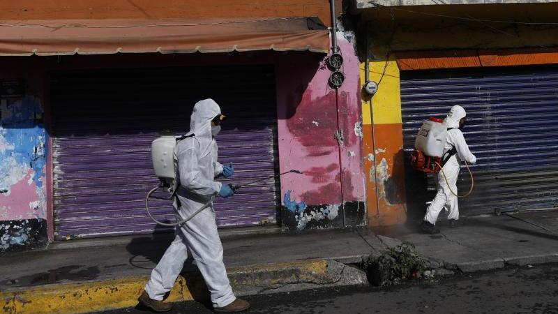 Coronavirus-Pandemie:In Mexiko-Stadt sprühen Arbeiter eine Desinfektionslösung auf die Straße. Foto: Rebecca Blackwell/AP/dpa