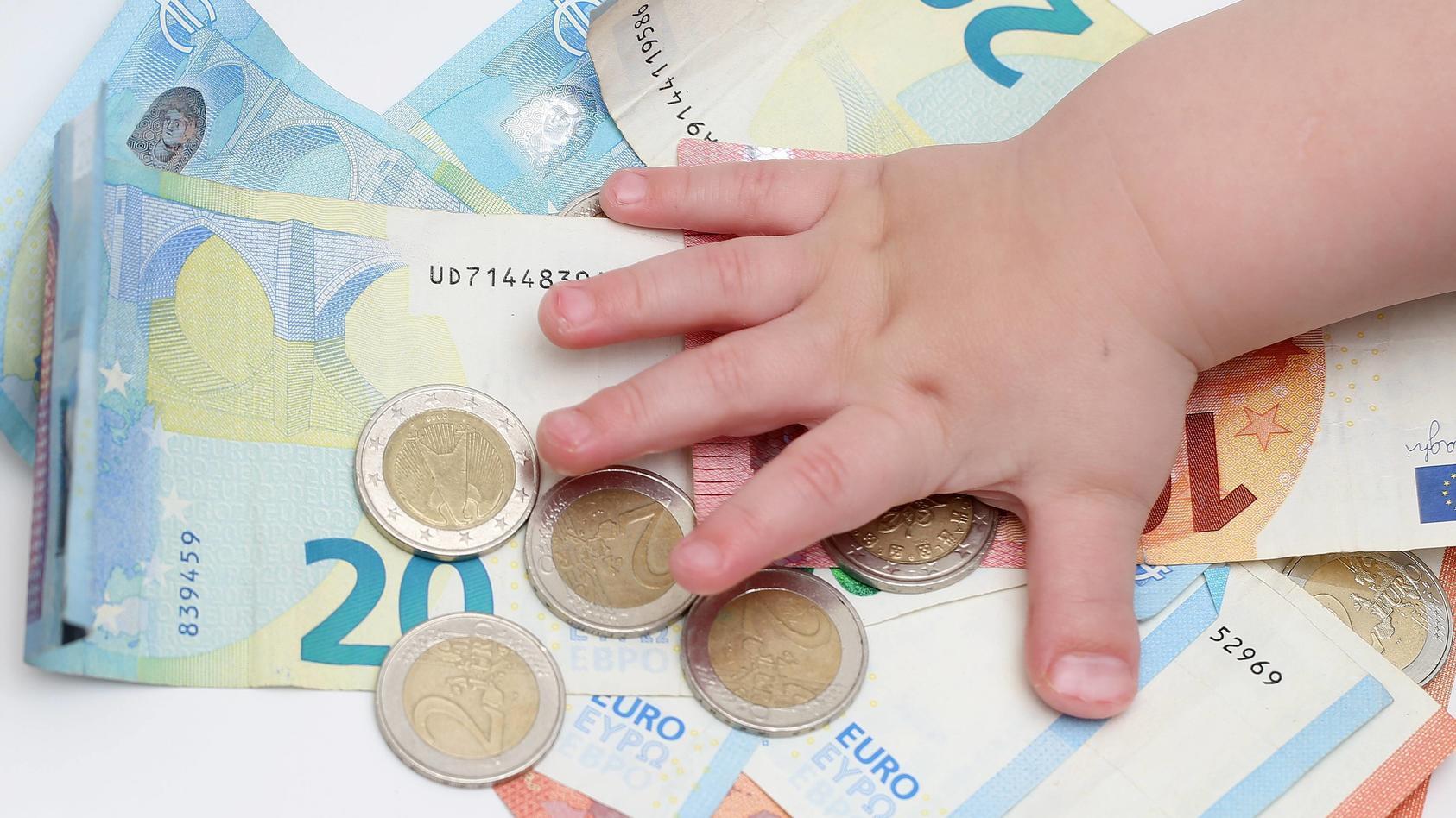 Symbolbild Geld 28.11.18, Symbolbild Geld, Kinderhand greift nach Stapel von 2 Euro Muenzen auf Geldscheinen Berlin Ber