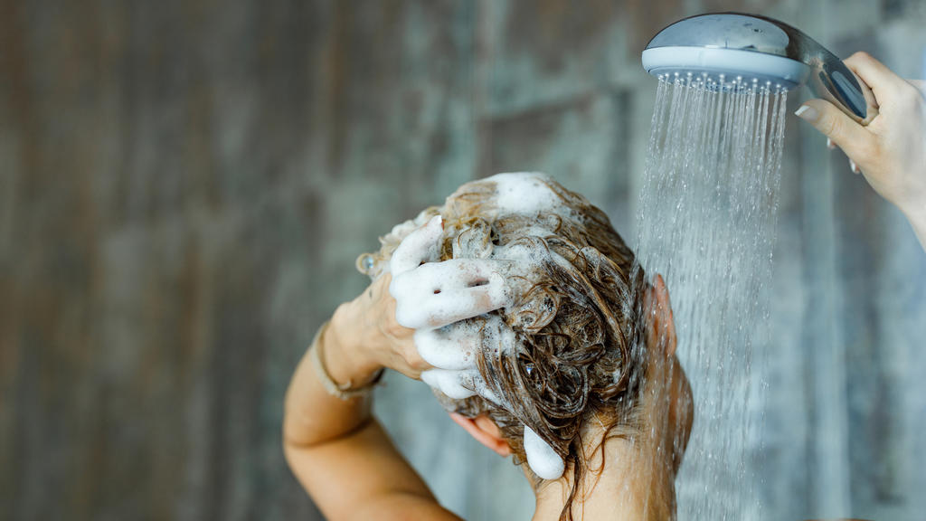 Fettiges Haar: Frau duscht