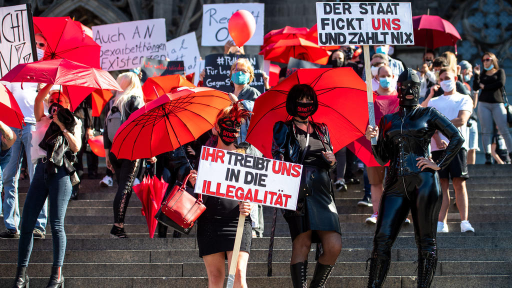 29.07.2020, Nordrhein-Westfalen, Köln: Eine Domina hält während einer Demonstration von Sexarbeiterinnen ein Schild mit der Aufschrift «Der Staat fickt uns und zahlt nix». Die Sexarbeiter demonstrierten gegen das Arbeitsverbot wegen Corona. Trotz Cor