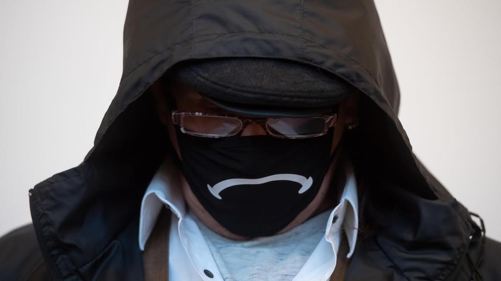 Der Angeklagte verbirgt sein Gesicht hinter einer Gesichtsmaske, einer Brille und unter einer Kapuze.