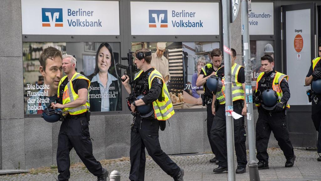 04.08.2020, Berlin: Polizisten stehen vor einer Bank im Stadtteil Wilmersdorf. Dort war ein brennender Geldtransporter gemeldet worden, wie die Feuerwehr mitteilte. Ein verletzter Mensch sei von einem Notarzt versorgt und in ein Krankenhaus gebracht