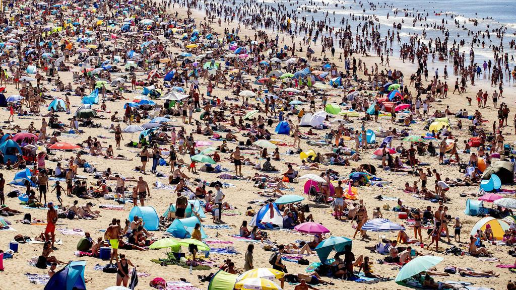 31.07.2020, Niederlande, Den Haag: Zahlreiche Menschen genießen das heiße Wetter am Strand von Scheveningen. Bei tropischen Temperaturen hat es einen Ansturm auf Strände in den Niederlanden gegeben. Die Bahngesellschaft NSwarnte in einem ungewöhnlic